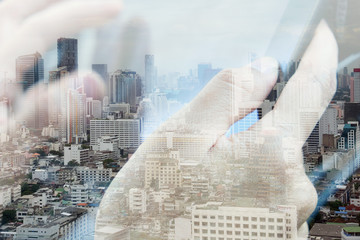 concept image of Business & technology,Abstract image of Using digital tablet double exposure and and cityscape background.