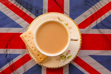 A cup of tea in a bone china cup and saucer on a union jack flag