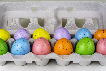 colored Easter eggs in grey cardboard egg carton
