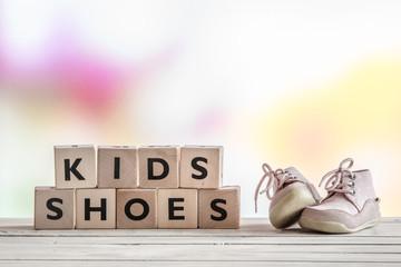 Kids shoes on a wooden desk