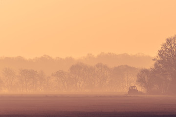 Misty morning with a tractor on a field