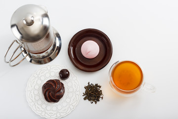 Glass tea pot with double sided wall glass cup full of green tea with sweets and biscuits