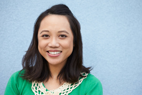 Portrait of smiling Asian woman against grey wall
