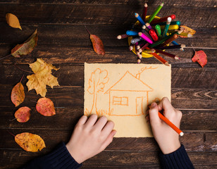 Close up of the hands of a child drawing a house on dark wooden