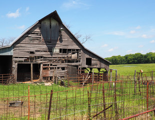 old wood barn by a rusty fence