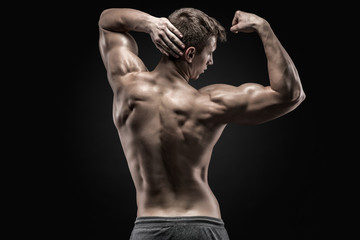 Healthy muscular young man showing back and biceps muscles Wall mural