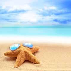 Summer beach with starfish in sunglasses. background sea.