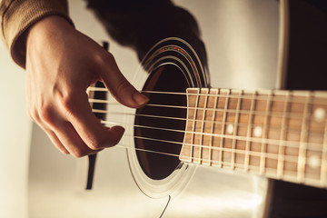 Woman playing guitar close-up shot