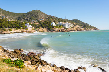Surfers enjoying the waves in a beach in Sitges, a small town near Barcelona.