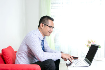 Asian business man using laptop computer with happiness