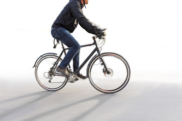 Man riding bike in blurred motion on white