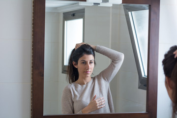 Portrait of a beautiful young woman combing hair and put on make up in front of her bathroom mirror.