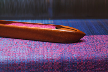 Weaving shuttle with thread on the blue warp