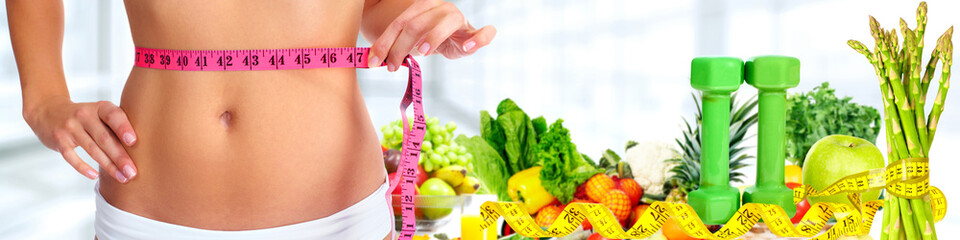 Woman abdomen with measuring tape over vegetables background.