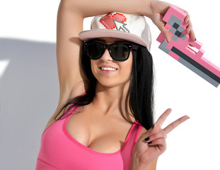 Sexy Brunette Woman in cap with pink pixels gun toy and sunglass