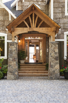 Stone and wood front porch and entry to upscale country house with paving stone driveway
