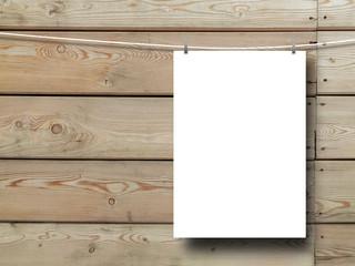 Close-up of one hanged paper sheet with clothes pins on horizontal brown wooden boards background