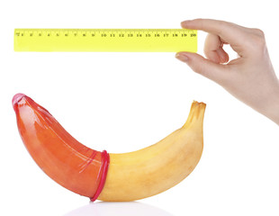 Female hand with plastic ruler and banana with condom isolated on white