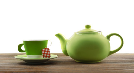 Cup of tea with tea bags and teapot on wooden background against grey background