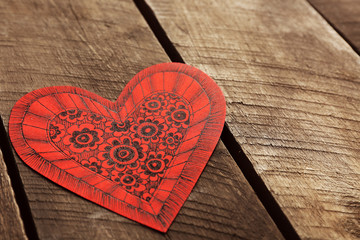 Red Valentine with doodle drawing on wooden background