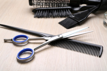 Barber set with tools on light wooden table, close up