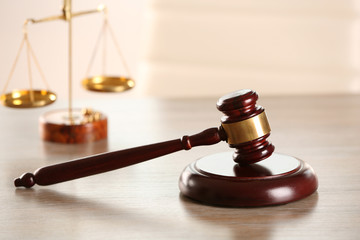 Gavel and scales of justice on wooden table indoors