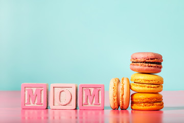 Colorful macarons with mom wood blocks on bright pastel background