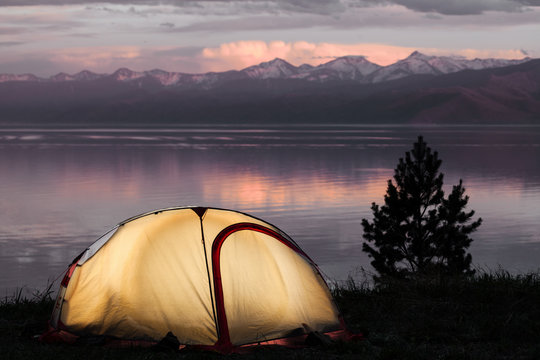 Tent across beautiful sunset on lake
