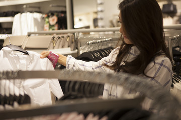Young women are enjoying shopping at clothing store