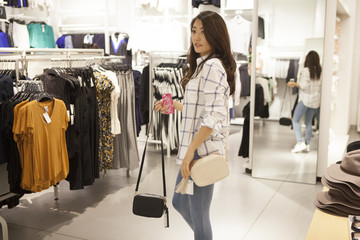 Young women are choosing the back while looking in the mirror in the shop