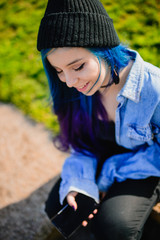Smiling teenage girl with blue hair using a smartphone
