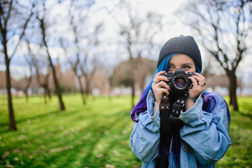 Teenager with blue hair making photographs