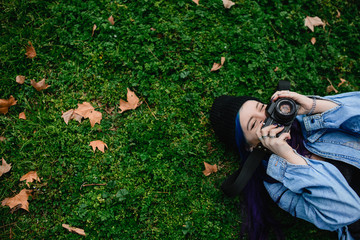 Teenage woman with blue hair lying taking pictures