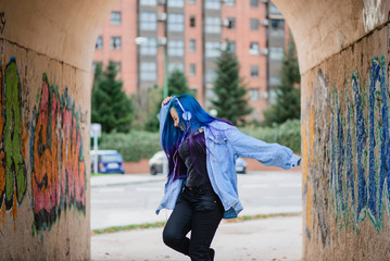 blue-haired teenager listening to music with headphones