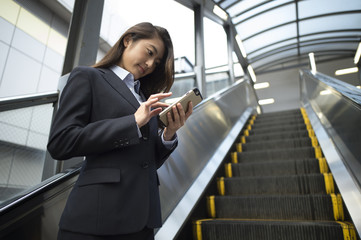 Business women who are using a smart phone in the escalator