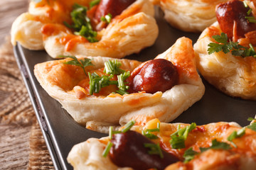 puff buns with sausage, cheese and onion macro in baking dish. horizontal