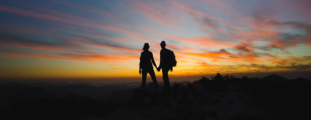 Silhouettes of two hikers with backpacks enjoying sunset view from top of a mountain. Travel concept