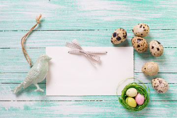 Decorative bird,  Easter eggs and empty tag on wooden background