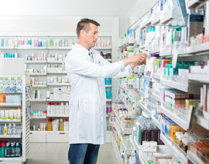 Female Chemist Arranging Products In Pharmacy