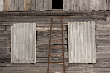 Old rusty ladder in front of log house.