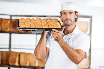 Baker Carrying Baking Tray On Shoulder At Bakery