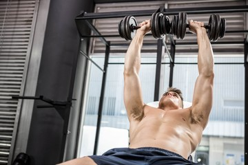 Shirtless man lifting heavy dumbbells on bench