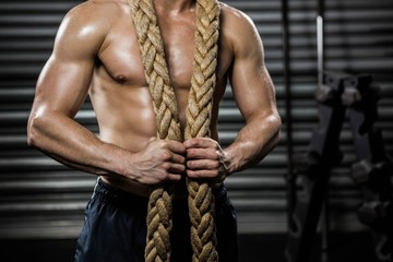 Shirtless man with battle rope around neck