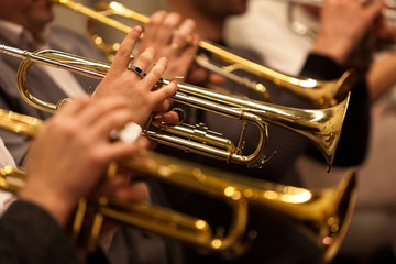 Trumpets in the hands of a musician in the orchestra closeup