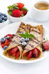 crepes with berries and chocolate sauce for breakfast on plate
