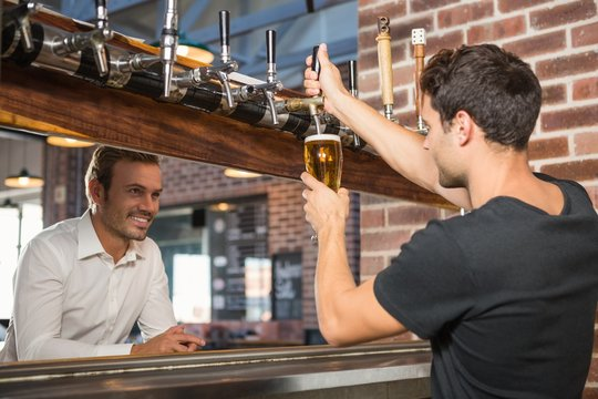 Handsome bar tender pouring a pint for a customer