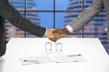 Businessmen's handshake after signing papers.