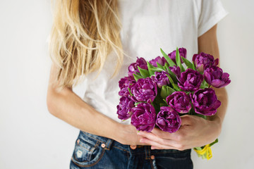 Violet tulips in girl's hands.
