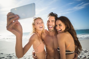 Happy friends taking selfie on the beach