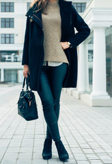 Woman in a sweater, black coat and pants holding a handbags whil